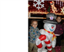 kid standing next to inflatable frosty the snowman