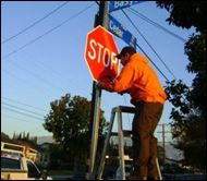 man working on stop sign